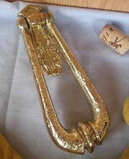 Aldaba, llamador en hierro dorado. Forma de péndulo.
